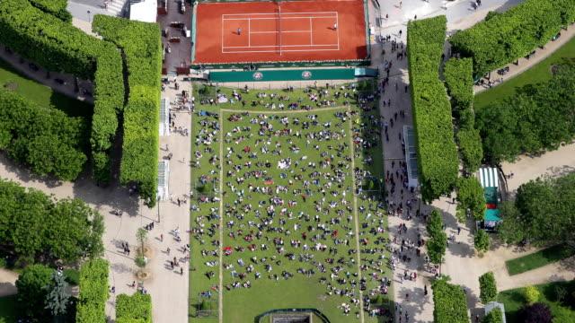 vidéos et rushes de vue aérienne de zoom avant de personnes allongé sur l'herbe - sunbathing