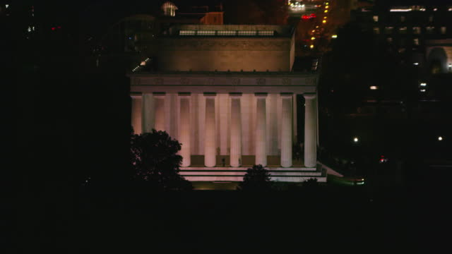 Aerial zoom in on Lincoln Memorial at night with lights on, DC