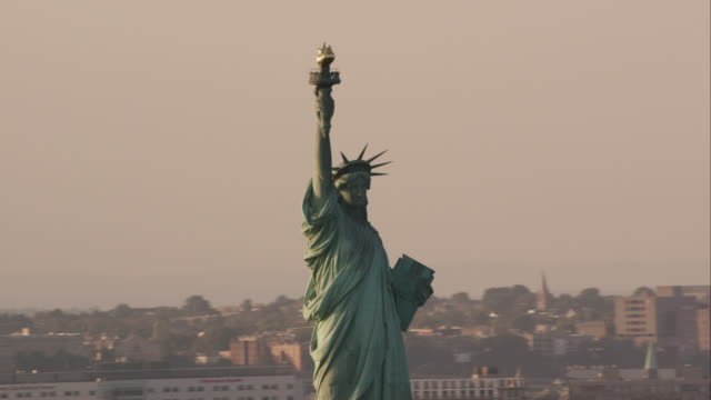 Aerial zoom in on Statue of Liberty in the late afternoon, NYC