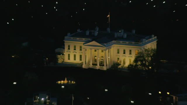 aerial zoom in on the white house from wide shot of dc at night - la casa bianca washington dc video stock e b–roll