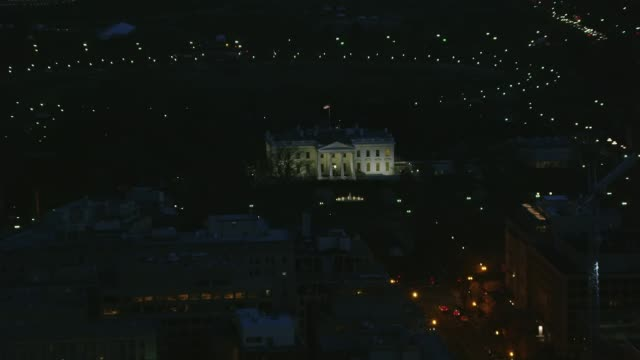 vídeos de stock e filmes b-roll de aerial zoom in on the white house from wide shot of dc at night - casa branca washington dc
