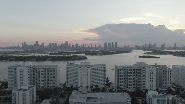 vídeos de stock, filmes e b-roll de aerial: zoom in shot of buildings in city by sea against sky during sunset, drone flying over cityscape - miami, florida - mais zoom