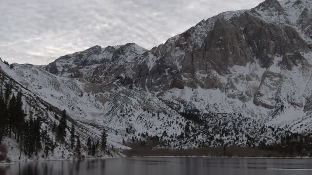 aerial zoom in shot of snowcapped mountains by convict lake against sky, drone flying over white landscape during winter - mammoth lakes, california - mammoth lakes video stock e b–roll