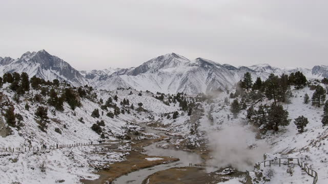 aerial zoom in shot of steam over creek amidst snow mountains, drone flying backward over hot creek geological site during winter - mammoth lakes, california - mammoth lakes video stock e b–roll
