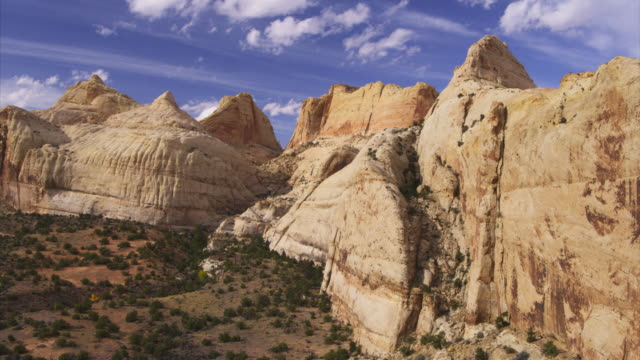 Aerial zoom in to rock formations in remote mountain landscape / Capitol Reef, Utah, United States