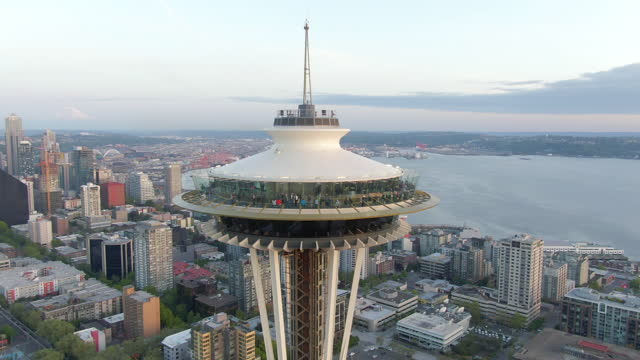 aerial zoom in to the observation deck of the space needle bustling with visitors set against a background of a elliott bay and downtown - seattle, washington - スペースニードル点の映像素材/bロール