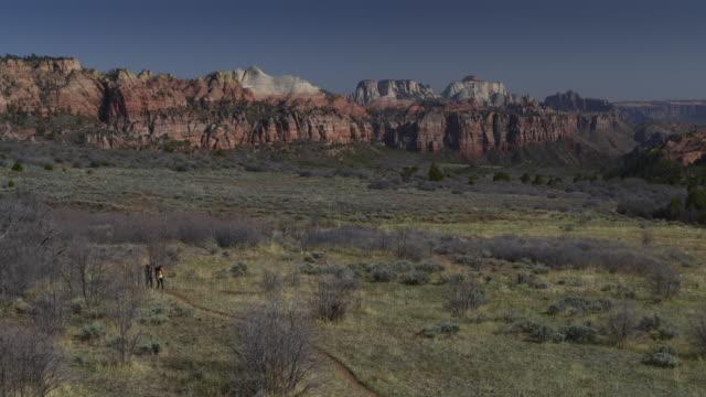 Aerial zoom in view of women hiking on trail near mountain range / Virgin, Utah, United States
