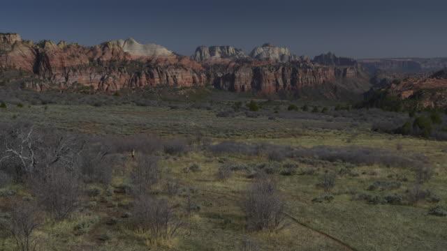 Aerial zoom in view of women running on trail near mountain range / Virgin, Utah, United States
