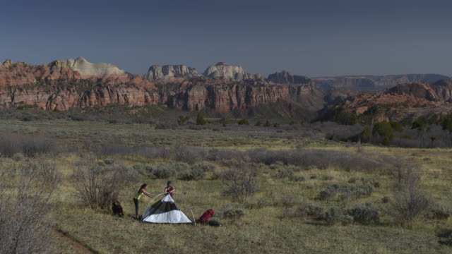 Aerial zoom in view of women setting up camping tent near mountain range / Virgin, Utah, United States
