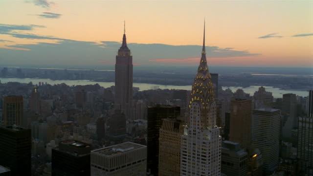 vídeos de stock e filmes b-roll de aerial zoom in zoom out empire state building and chrysler building / manhattan at sunset /new york city - prédio chrysler
