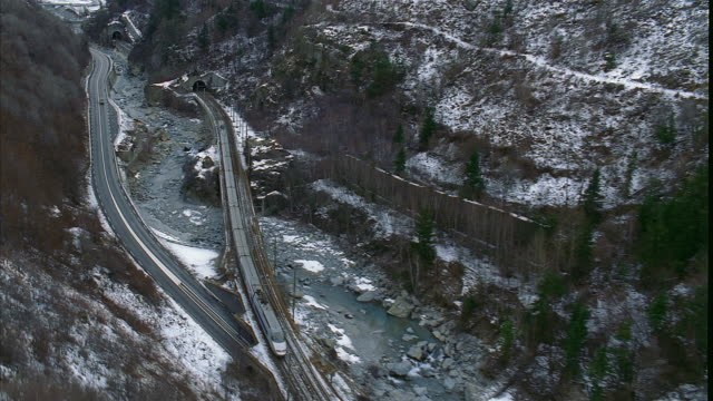 aerial zoom in zoom out following passenger train in and out of tunnels through swiss alps / switzerland - passenger train bildbanksvideor och videomaterial från bakom kulisserna