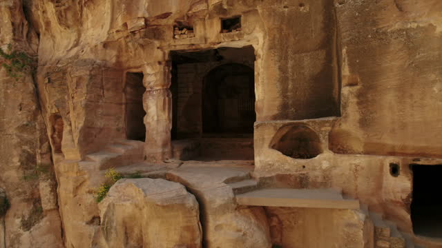 aerial zoom into a villa carved into rock at petra - stone material stock videos & royalty-free footage