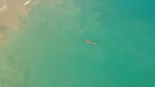 Aerial Zoom: Man Floating in the Ocean