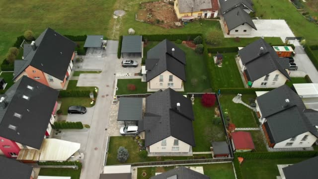 aerial zoom out footage of family homes in the suburbs build next to each other - neighbour stock videos and b-roll footage
