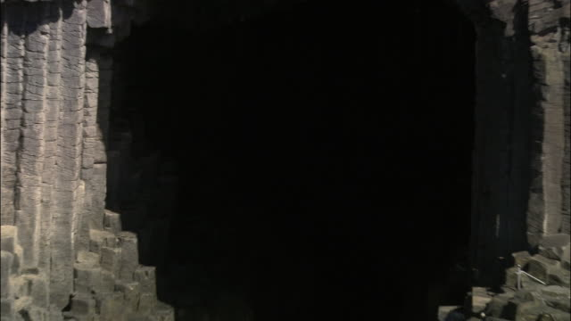 vídeos de stock, filmes e b-roll de aerial zoom out from dark entrance to fingal's cave to view of grotto in cliff / staffa island, scotland - grotto cave