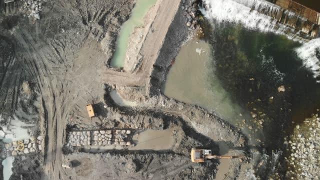 aerial zoom ur mark byggarbetsplats - damm människotillverkad konstruktion bildbanksvideor och videomaterial från bakom kulisserna