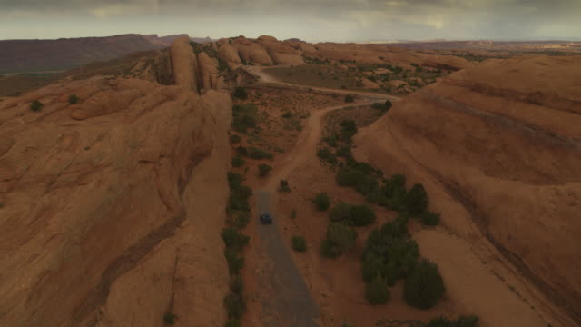 Aerial zoom out of distant cars driving on trail in sand flats under clouds / Moab, Utah, United States