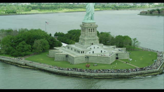 aerial zoom out orbit statue of liberty on 'the french will never forget' - 自由の女神点の映像素材/bロール