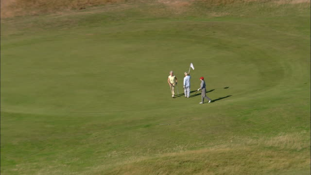 vídeos de stock e filmes b-roll de aerial zoom out over three women golfing on the old course at st. andrews links / fife, scotland - golfe