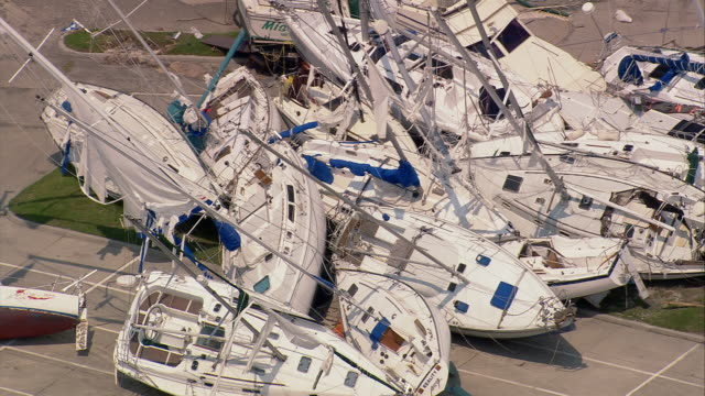 vídeos de stock, filmes e b-roll de aerial zoom out piles of destroyed yachts blown by storm at south shore harbor / new orleans louisiana - 2005