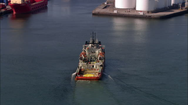 aerial zoom out rear view of oil ship coming into aberdeen port / aberdeen, scotland - oil rig supply ship stock videos and b-roll footage