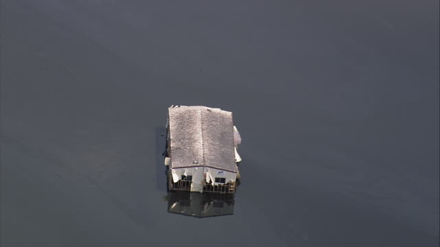 vídeos y material grabado en eventos de stock de aerial zoom out solitary house submerged in oily water / flooded neighborhood / new orleans, louisiana - 2005