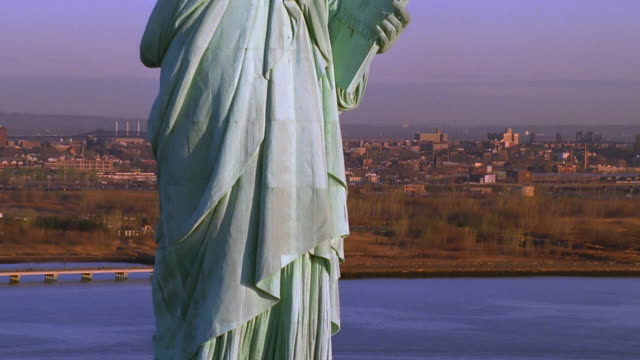 aerial zoom out tilt up american flag to statue of liberty / new york city - statue stock videos & royalty-free footage