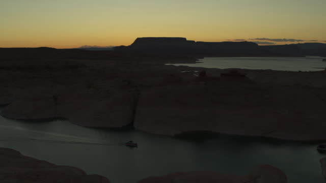 vídeos y material grabado en eventos de stock de aerial zoom out view of boat in lake near desert landscape at sunset / glen canyon, utah, united states - lago powell