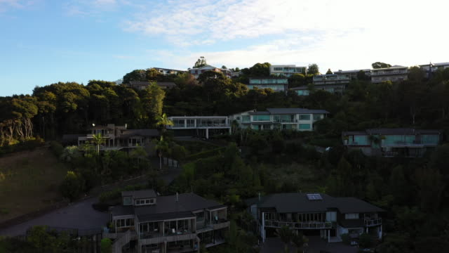 vidéos et rushes de aerial zoom out view of houses on hill / paihia, new zealand - bay of islands nouvelle zélande