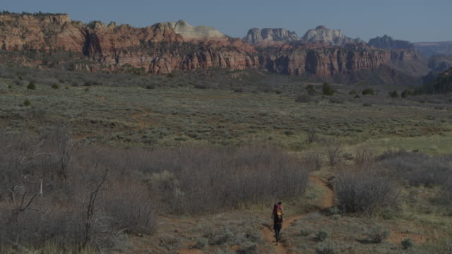 Aerial zoom out view of women hiking on trail near mountain range / Virgin, Utah, United States