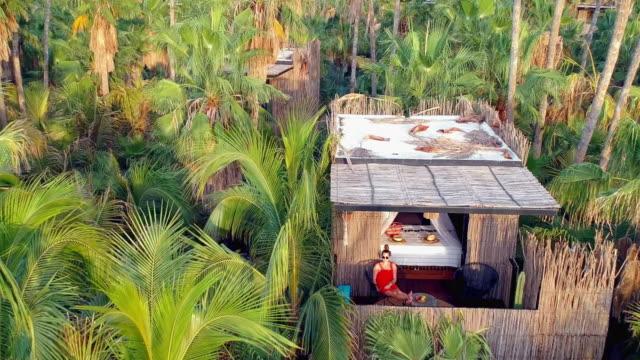 vídeos de stock, filmes e b-roll de aerial zoom: woman in jungle hut relaxing in mexico - cabana casa