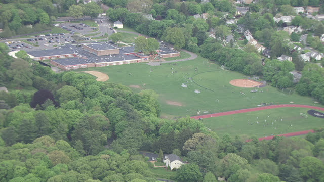 aerial zoom-in on athletic fields of elementary or middle school. baseball diamond, track and field, playground, students visible playing on field. - education building stock videos & royalty-free footage