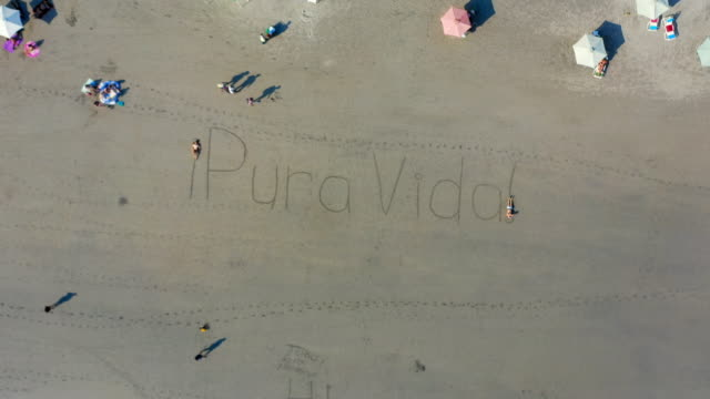 """vídeos de stock e filmes b-roll de aerial: zooming in at sand writing saying """"pura vida!"""" and two people lying on the exclamation marks - playa espadilla, costa rica - ponto de exclamação"""