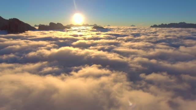 vídeos de stock, filmes e b-roll de aérea: acima das nuvens com luz dourada - no alto