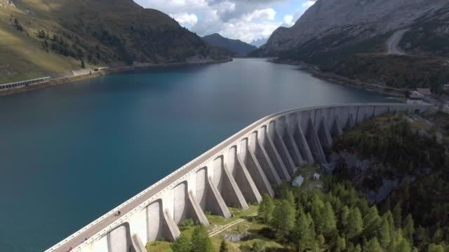 antenn: dammen på alpian lago fedaia, italien - damm människotillverkad konstruktion bildbanksvideor och videomaterial från bakom kulisserna