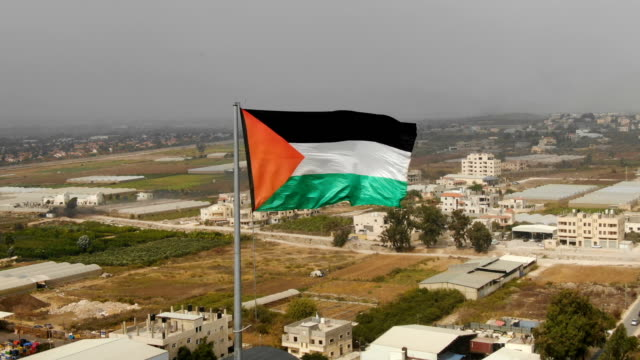 aerial/flag of palestine blowing in the wind with arab palestinian city in back - palestinian stock videos & royalty-free footage