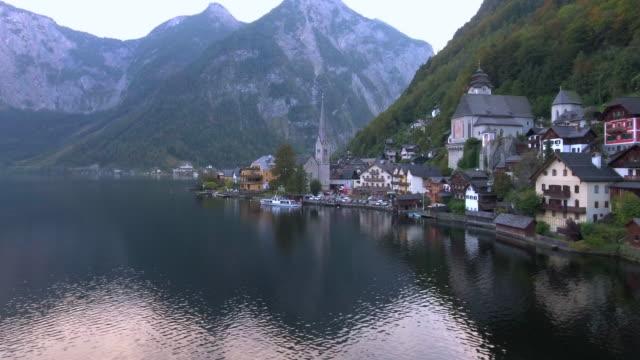 aerial:hallstatt austria in a valley - dachstein mountains stock videos and b-roll footage