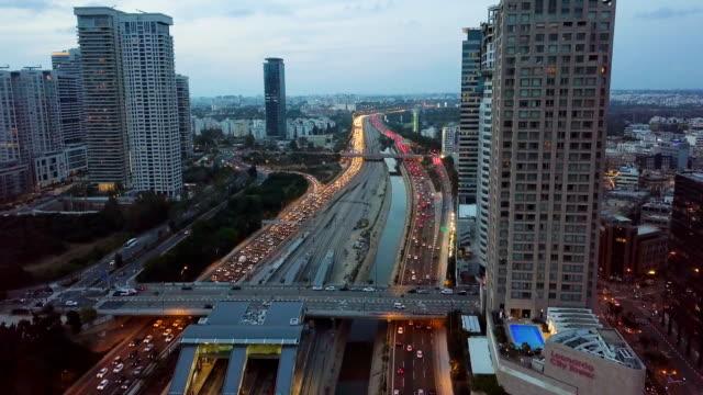 aerial/high buildings of tel aviv skyline at sunset - major road stock-videos und b-roll-filmmaterial