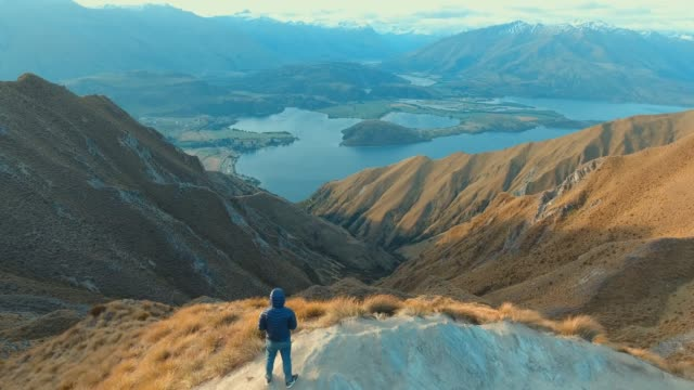 aerial:man at the top of mountain - new zealand stock videos & royalty-free footage