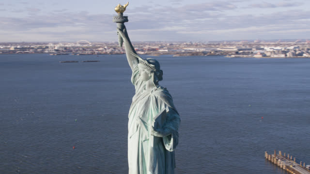 aerialof statue of liberty in new york harbor. landmarks. new jersey and boats or ferries in bg. - weibliche figur stock-videos und b-roll-filmmaterial