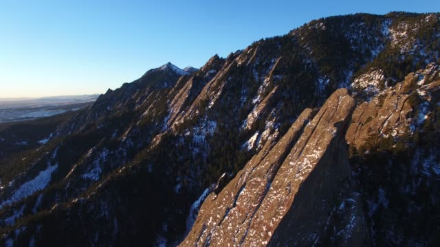 aerial/pan right: rocky mountains with evening sun and bright blue sky - kirchturmspitze stock-videos und b-roll-filmmaterial