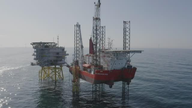 vidéos et rushes de aerials hornsea wind farm jack up vessel and power substation - montage séquentiel