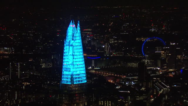 aerials london landmarks lit up blue including the shard and the millenium wheel as the nation applauds the nhs for their coronavirus work during... - nhs stock videos & royalty-free footage