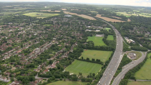 aerials of countryside and housing around the m25 motorway near heathrow airport - housing development stock videos & royalty-free footage