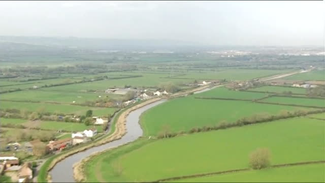 aerials of dredging on somerset levels flooded fields and ditches / river / village next to river / river / diggers by river dredging / digger... - somerset levels stock videos and b-roll footage