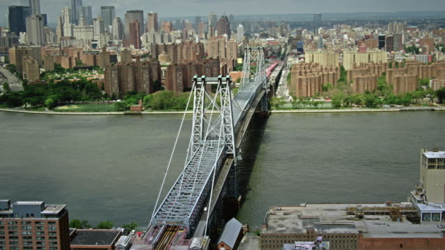 aerials of east river, new york city, following williamsburg bridge from brooklyn to manhattan - williamsburg bridge stock videos & royalty-free footage