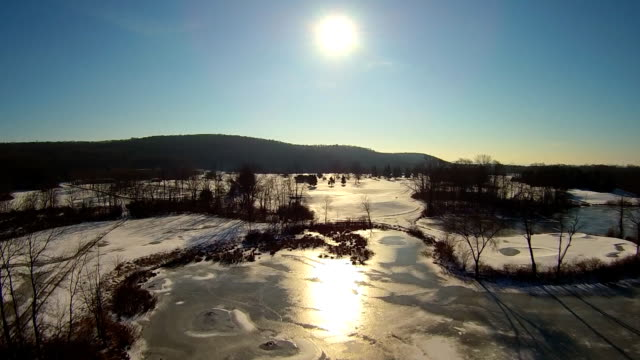 aerials of hudson valley winter views, including a small lake, and snowy fields into sun - hudson valley stock videos and b-roll footage