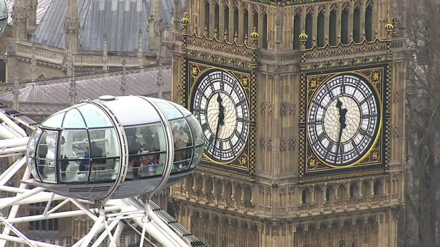 Aerials of London Westminster Houses of Parliament Big Ben and London eye on the River Thames Union Jack flying on March 20 2014 in London England