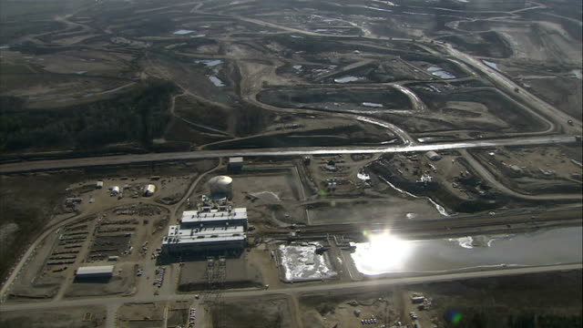 Aerials of mines at Athabasca Oil Sands Air views of Suncor oil extraction buildings and mining area / White storage tanks and River Athabasca PAN to...