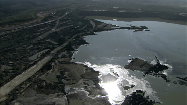 Aerials of mines at Athabasca Oil Sands More tailing pond aerials with sun glistening on oily surface good shot / More airviews of Suncor mines and...
